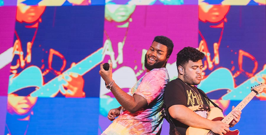 Colorful photo of Khalid and guitarist on stage rocking out