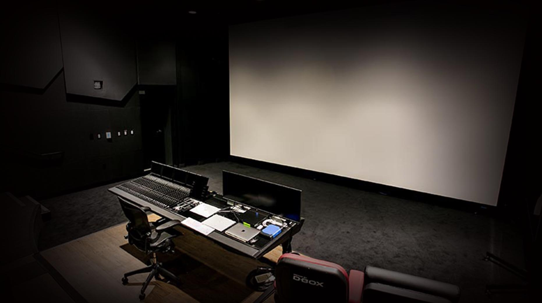Image of Dolby Atmos and Pro Tools workstation in front of large theatre screen