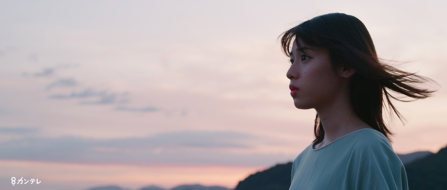 a woman seen in profile against a sunset in a still from three trees