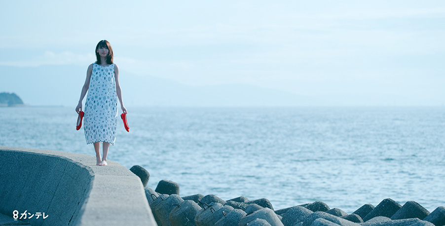 a woman walks along a sea wall in a still from the movie three trees