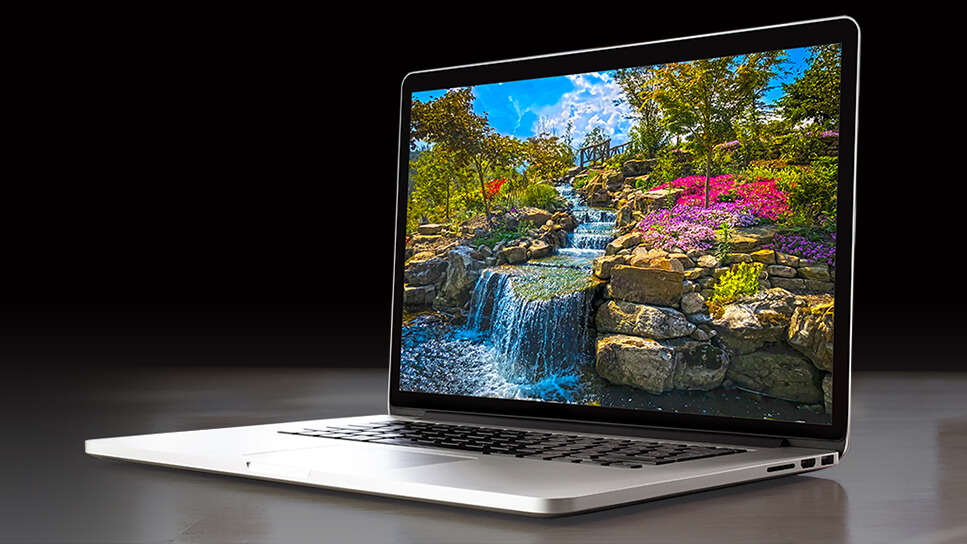 HDR image of a waterfall with colorful flowers displayed on a laptop