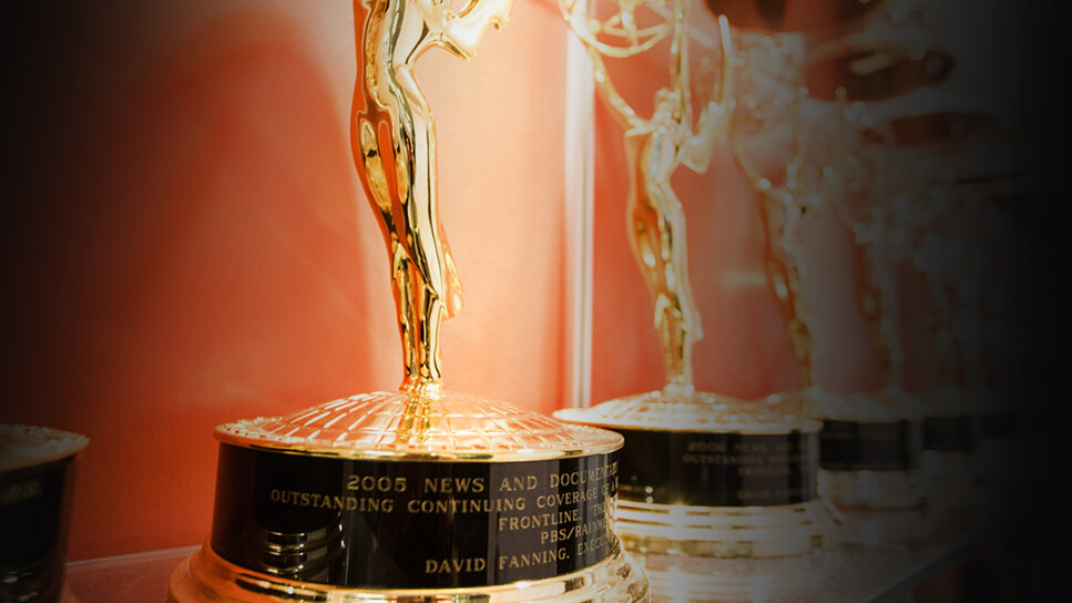 Close-up of Emmy Awards lined up in a row