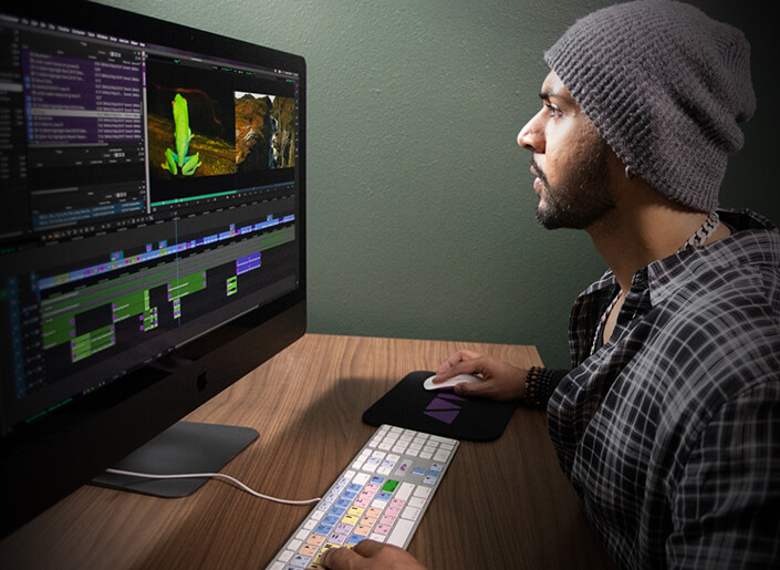 Video editor at desk looking through footage on a single screen
