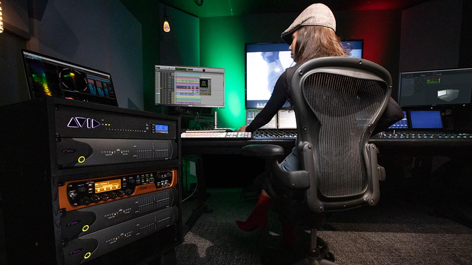 Back of female editing Dolby Atmos session in a smaller audio post suite using Avid S6 and Pro Tools audio production software