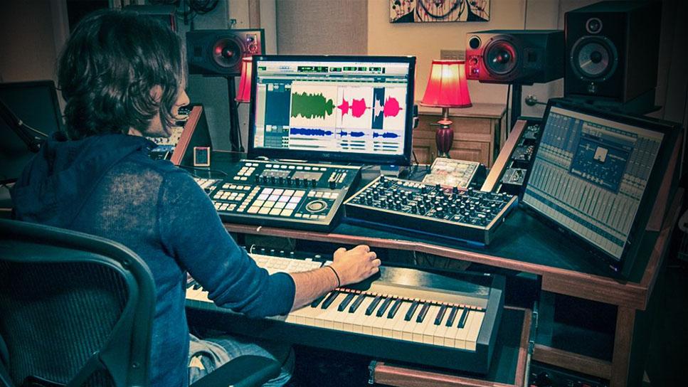 Tecladista masculino que edita um clipe de áudio no software de música Pro Tools