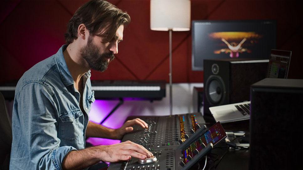 Mixer masculino usando Avid S3 e Dock para mixar uma sessão no software de música Pro Tools
