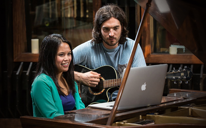 Female piano player and male acoustic guitarist playing as a duo while reading music from a laptop on the piano