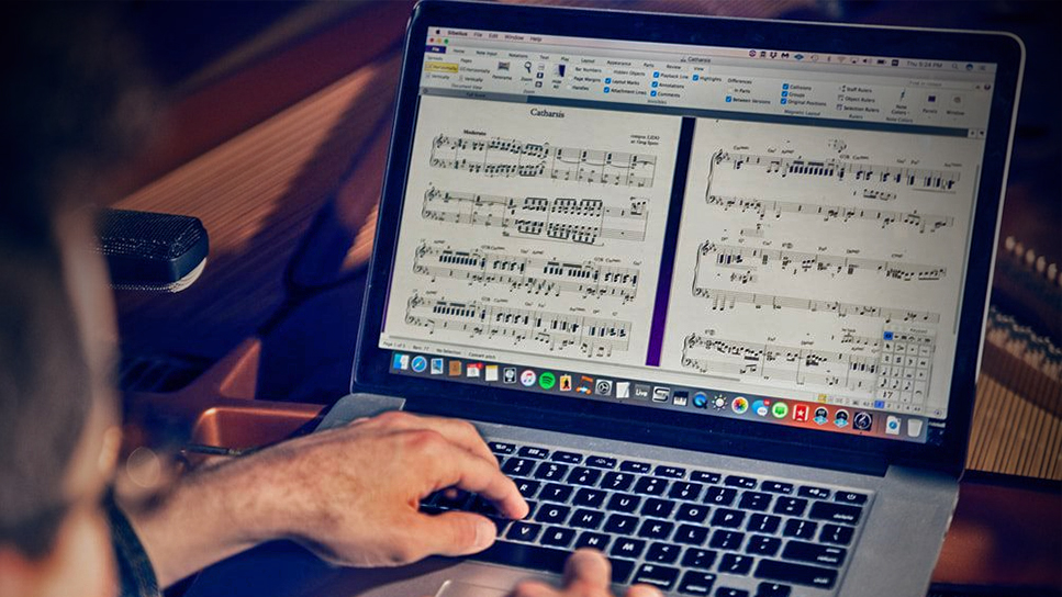 Close-up of a man's hands on a laptop keyboard, engraving a score in Sibelius music notation software displayed on the screen