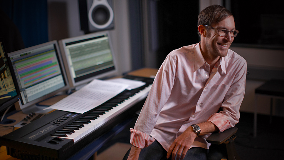 Male orchestrator smiling while turning away from his keyboard with sheet music laid on top and music notation software on two screens behind it