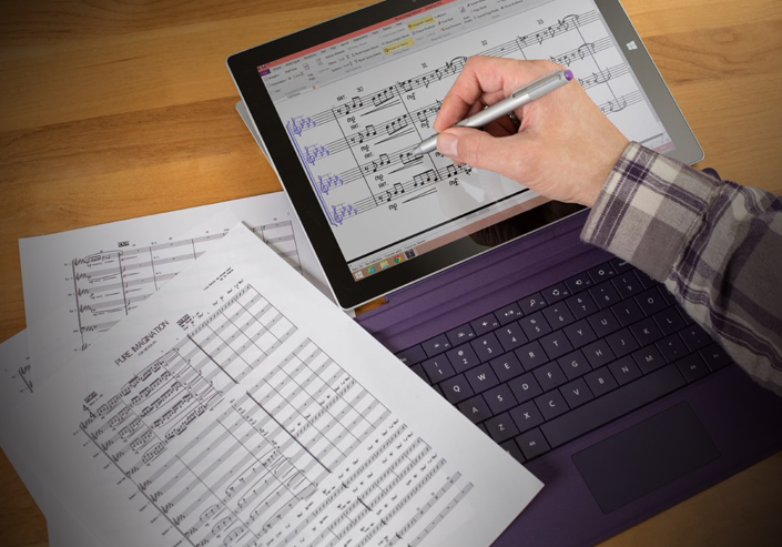 A person's hand using a Surface Pen to write music notes in Sibelius music composing software on a Surface Pro tablet