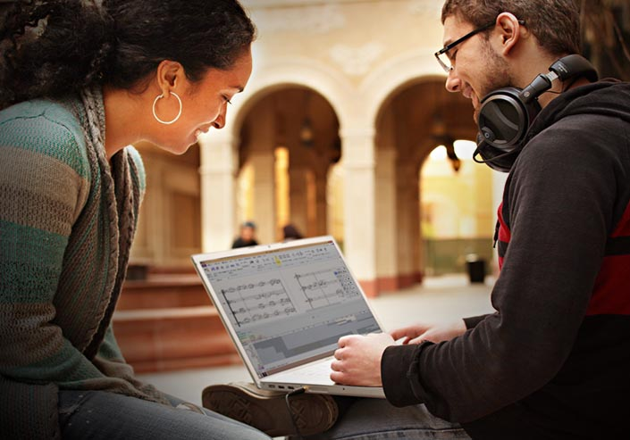Male student with headphones around his neck working on a score using music notation software on his laptop while a female student looks on