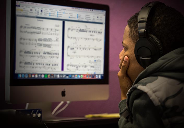 Male student wearing headphones looking at a Sibelius music notation software score on a computer display