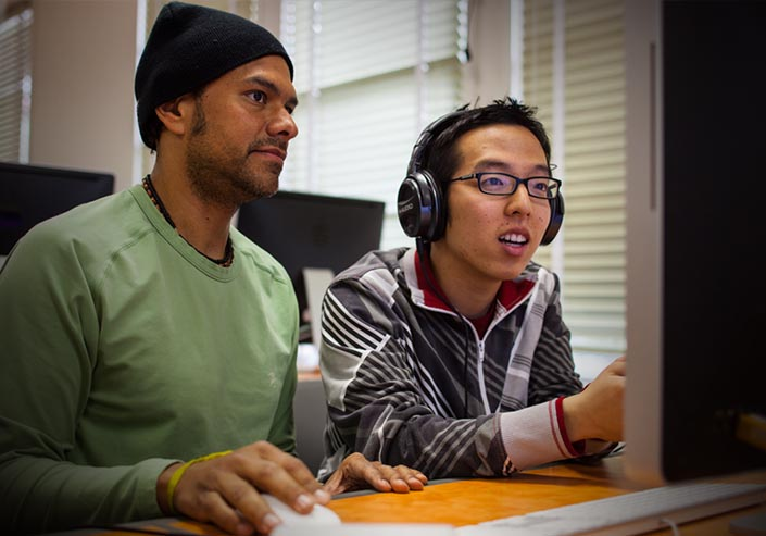 Male teacher using a mouse sitting next to a male student wearing headphones, looking at an unseen score on a computer display