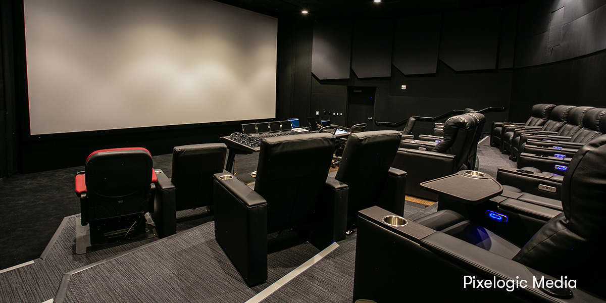 Photo of an immersive mixing theatre room featuring a workstation with Dolby Atmos, Pro Tools, and Avid S6
