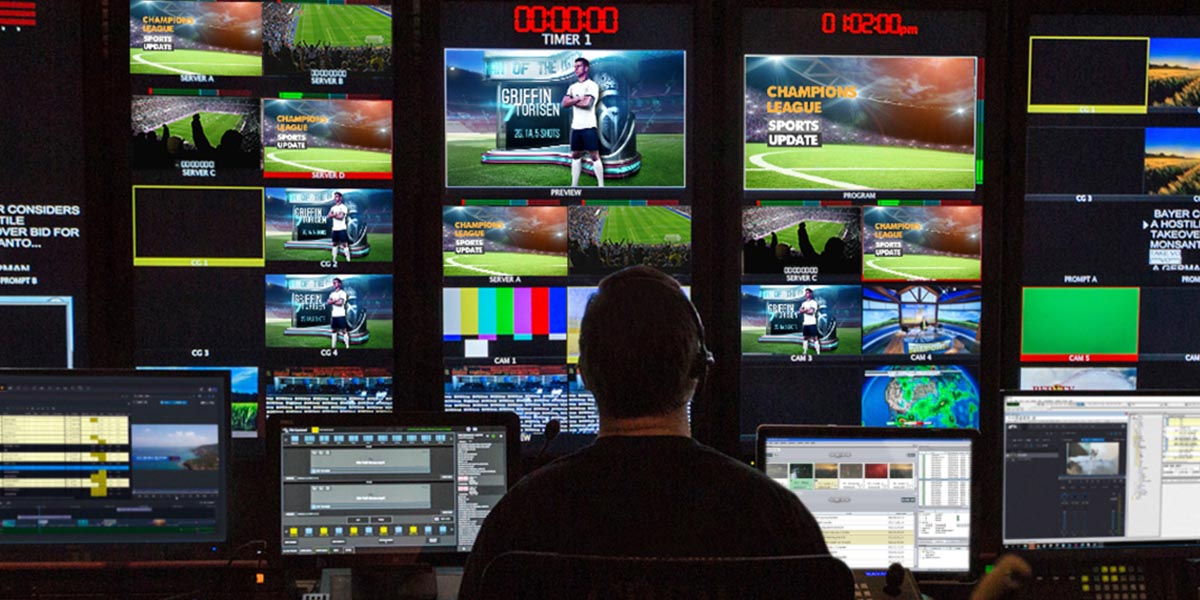 Man watching multiple monitors showing different angles of a sports game coverage