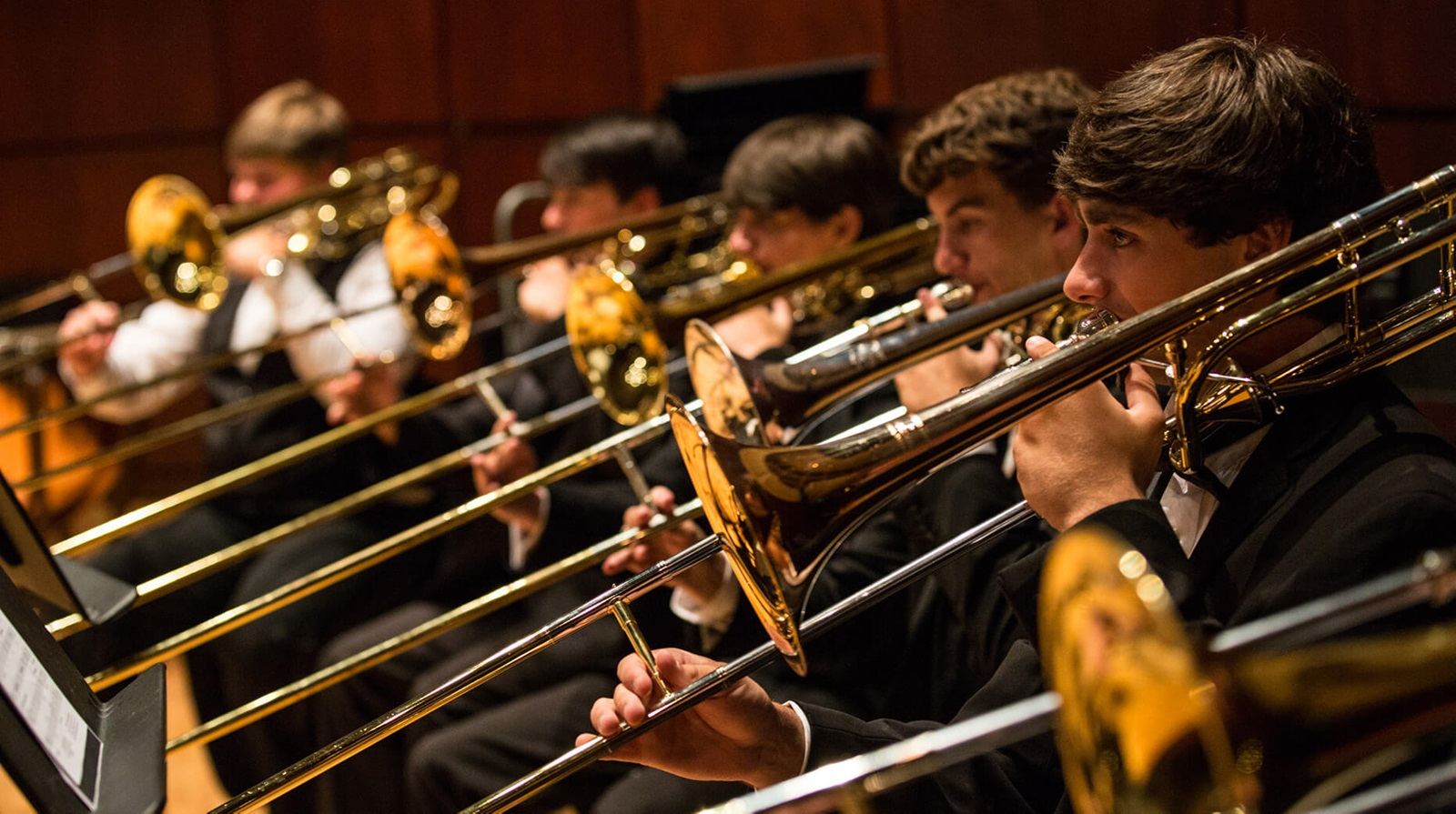 row of trombonists performing in an orchestra