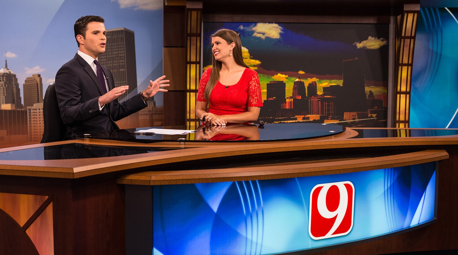 two anchors seated at news desk in studio