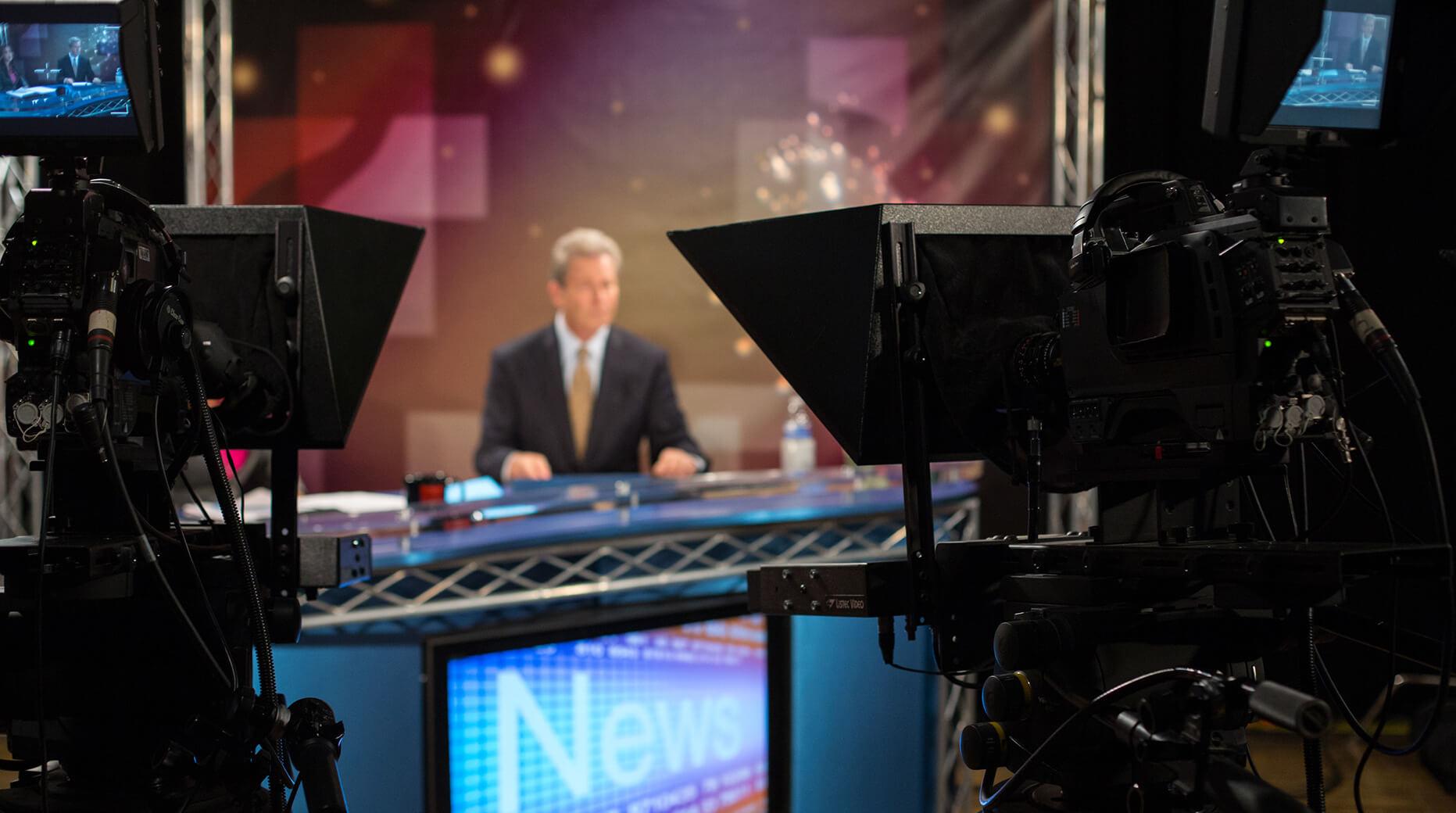 news anchor at anchor desk as seen from behind camera
