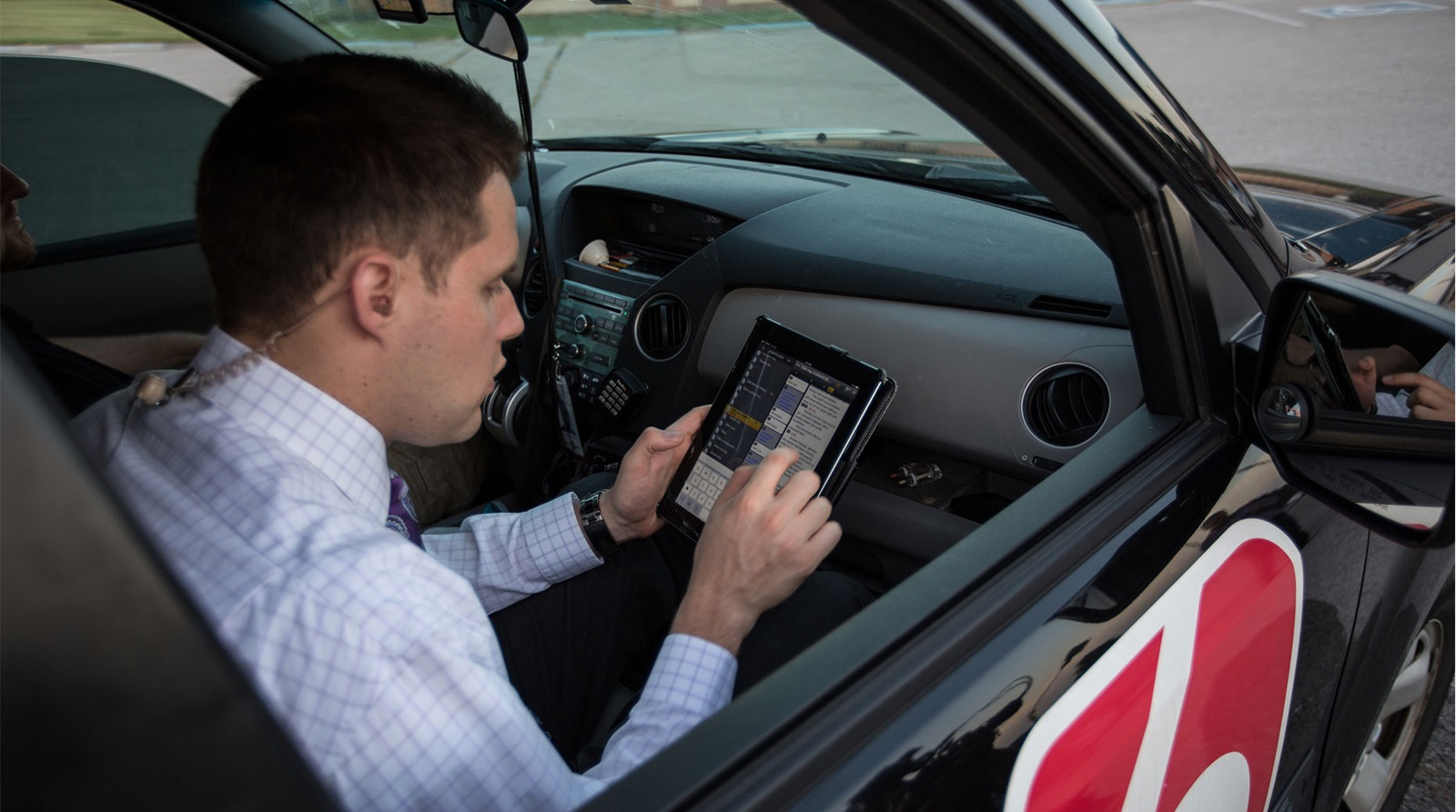 A field reporter sitting in a car uses a mobile app for news production.