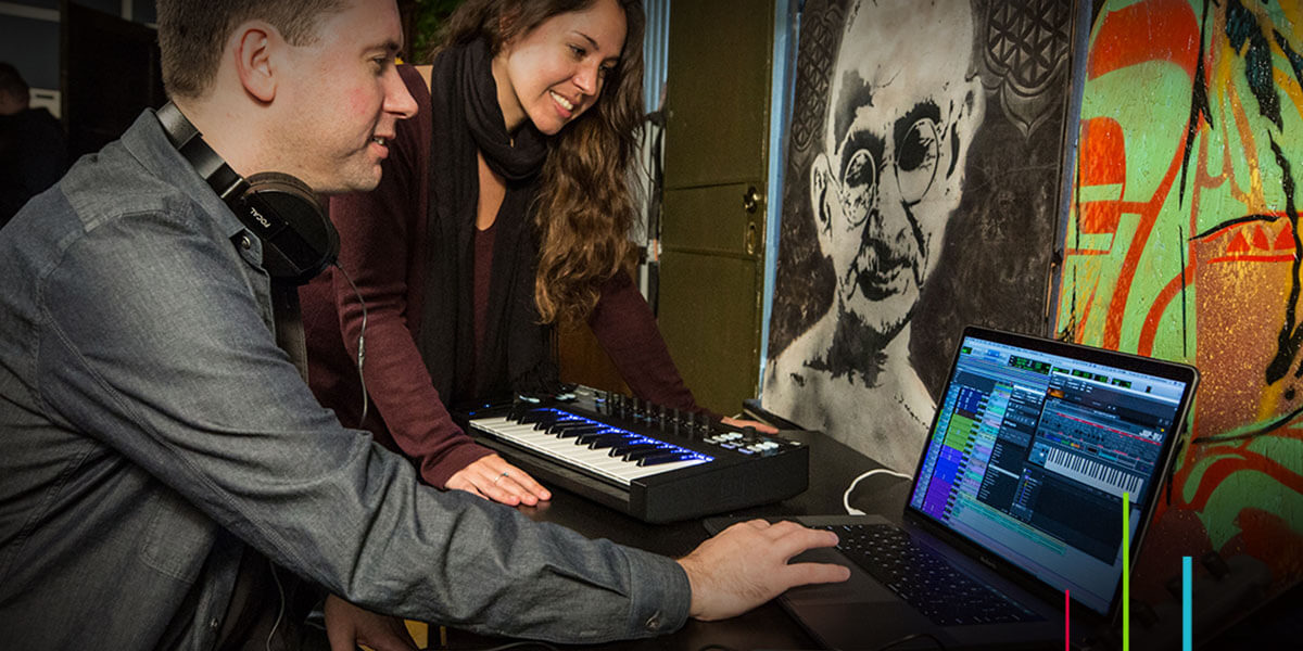 Man and woman using Pro Tools music software on laptop with MIDI keyboard