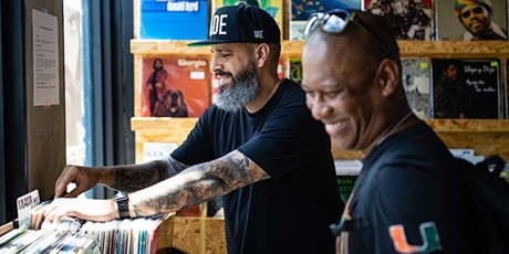 A man with tattooed arms wearing black cap flipping through a stack of vinyl records and another man with eyeglasses raised on his head